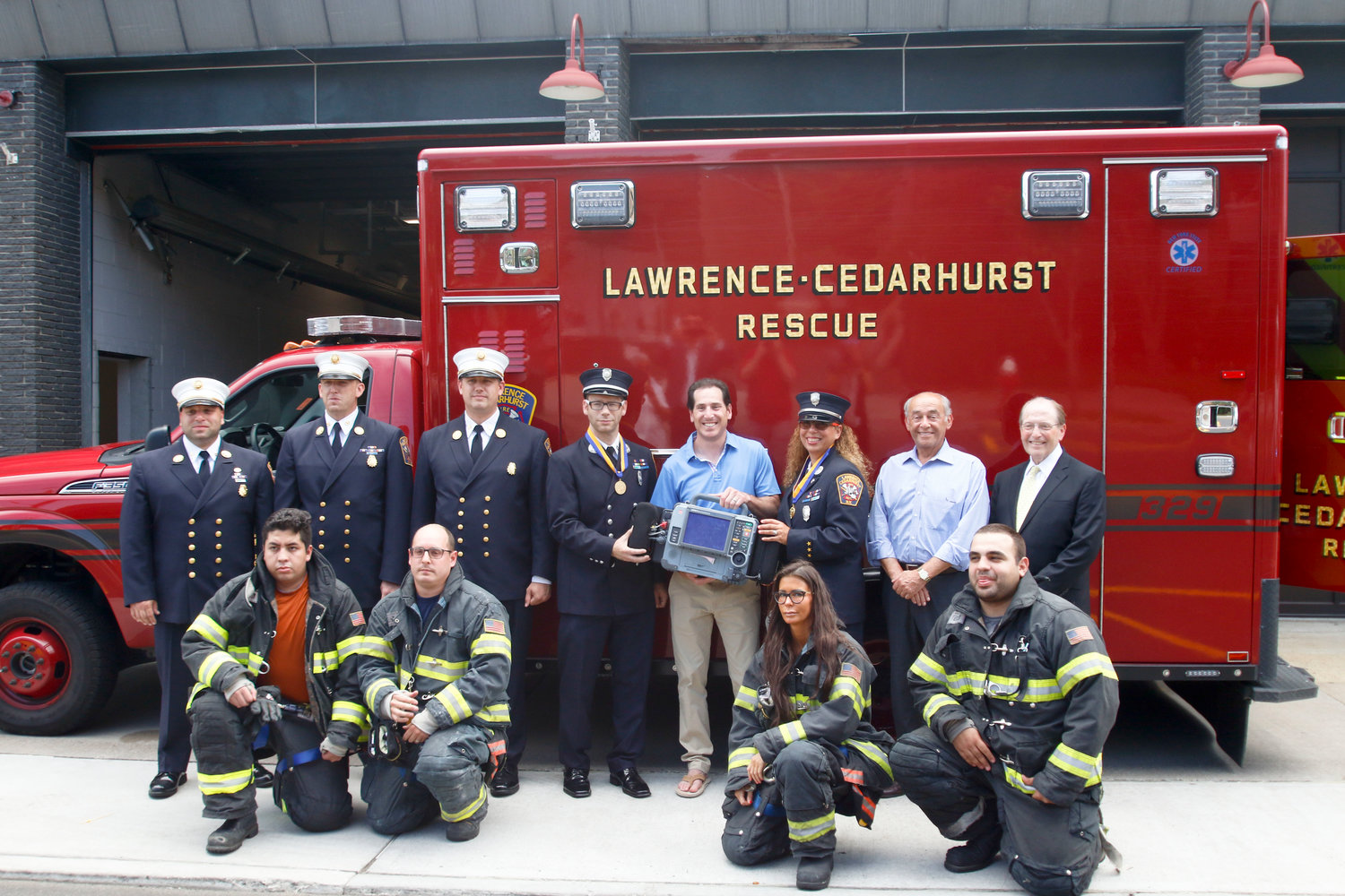 Life-saving equipment, including a new ambulance were dedicated by the Lawrence Cedarhurst Fire Department. State Sen. Todd Kaminsky held the defibrillator flanked by Liberty Medal recipients Meyer Adler and Shoshana Weiner. On the far right was Cedarhurst Mayor Benjamin Weinstock and second from right Lawrence Mayor Alex Edelman.