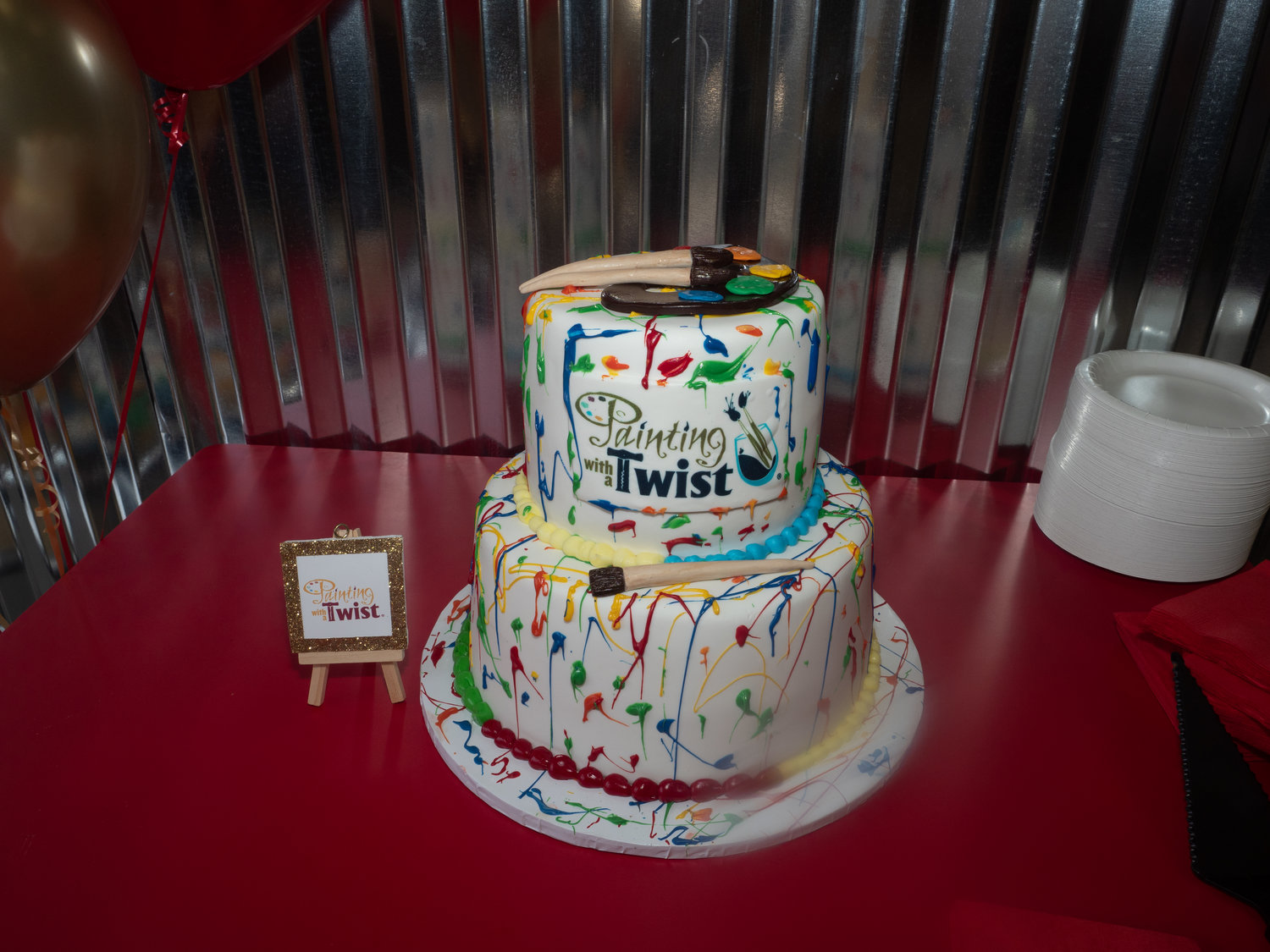 Guests celebrated with wine and a colorful painting-themed cake.