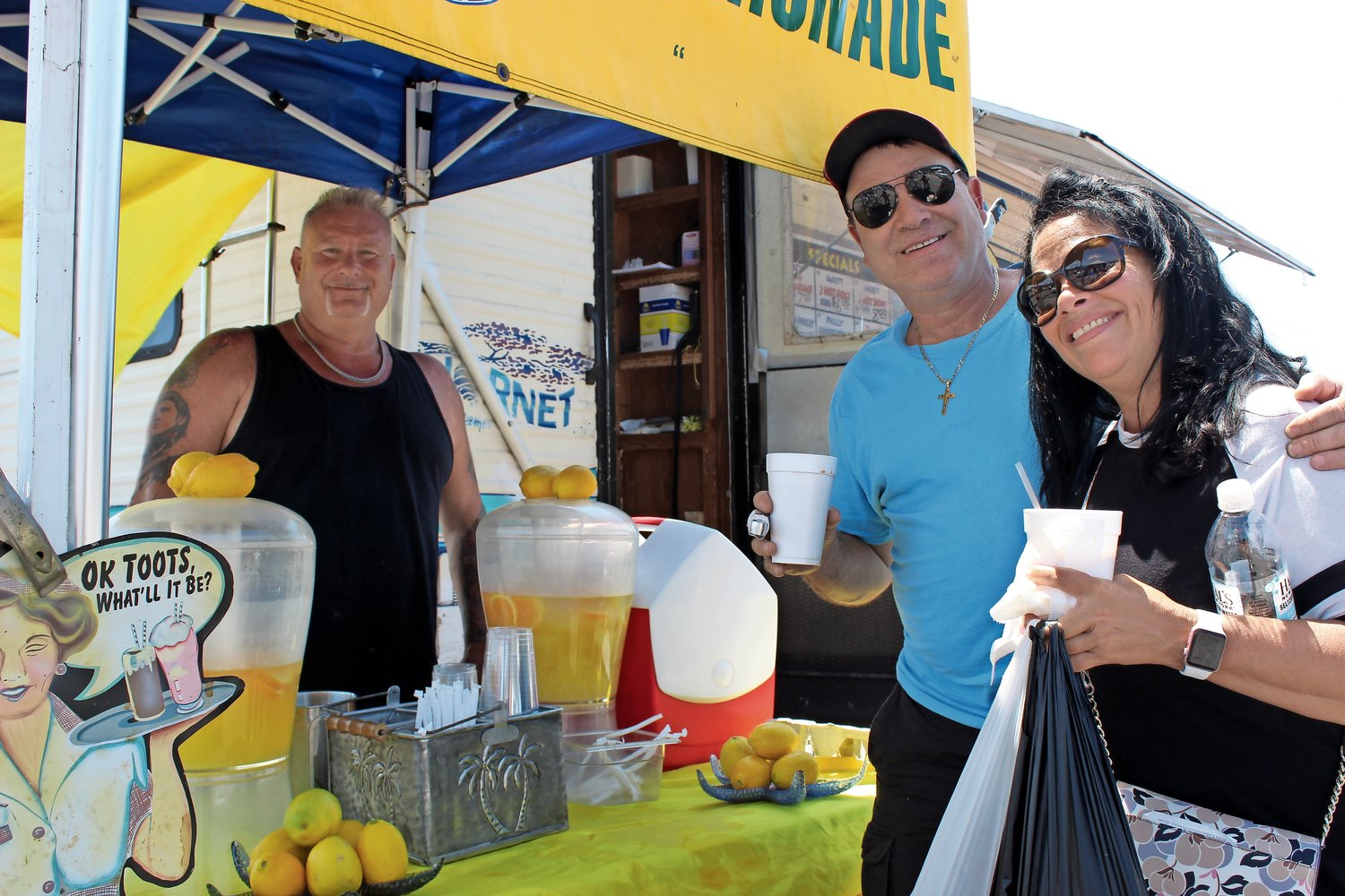 Sal Briganti, left, of Bellmore, kept shoppers satiated with lemonade, snacks and hot dogs. Babylon couple Bill and Sue Amato, right, were happy to oblige.