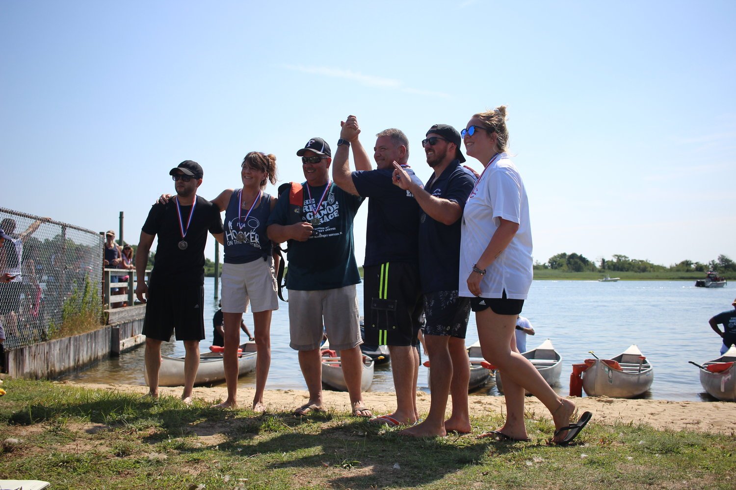 Freeport Mayor Robert Kennedy, third from left, and Legislator Steve Rhoads, third from right, win first place in one of the races at the annual Great Canoe Race in Cow Meadow Park.