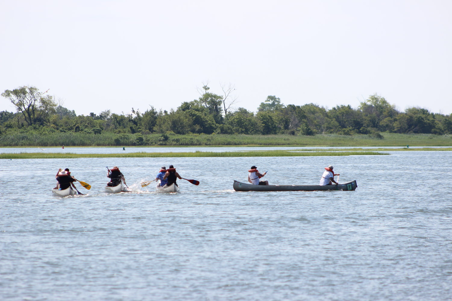 A canoe race competitors vie for first place medals during a morning race.