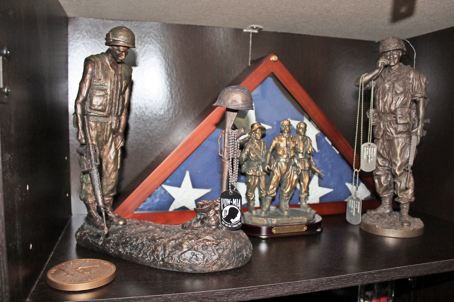A display case in a spare room of Jantz's Patchogue home features soldier statuettes, dog tags, books and other war memorabilia.