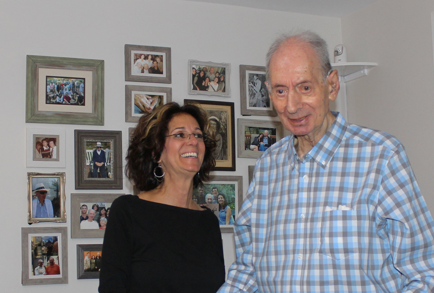 Stanley Shubin, who will be 99 on Aug. 25, lives in East Meadow with his daughter Randi Shubin Dresner. Behind them is a wall of photos commemorating some of the highlights of Shubin's life.