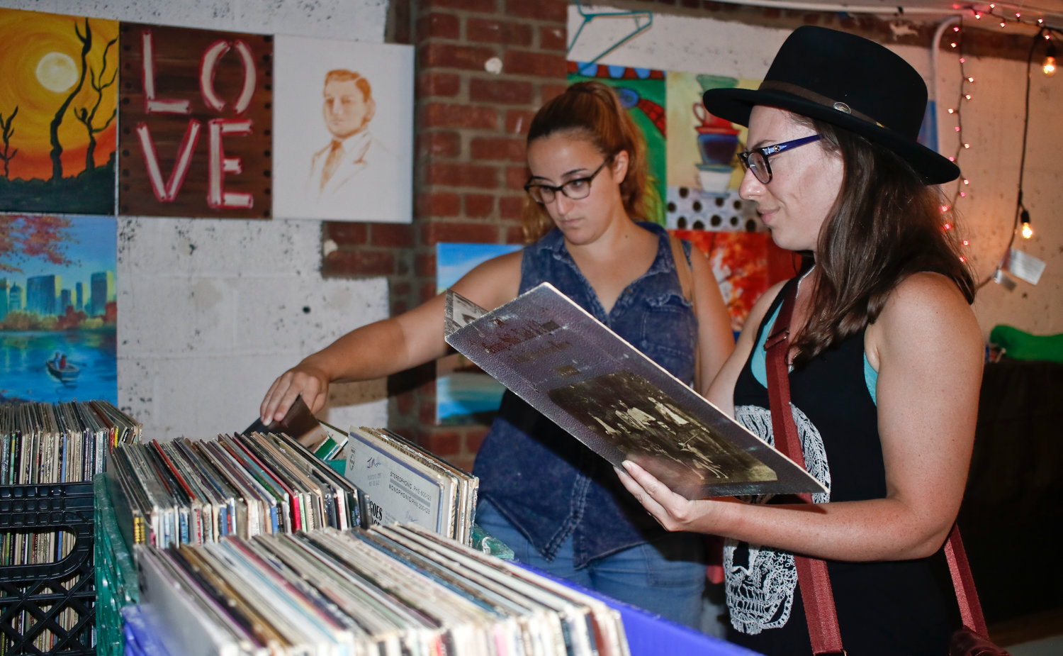 Dawn Buscemi checked out a Crosby, Stills, Nash & Young record while her friend, Liz Pasipanki, browsed through the rest of the collection during Creative Corner's Woodstock festival last Sunday.