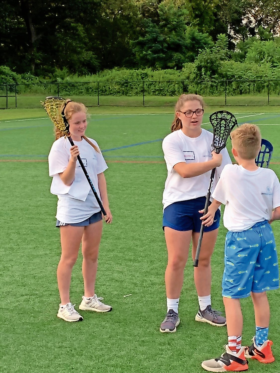 Emma Madden and Mackenzie Creagh teach a camper how to hold the lacrosse stick.