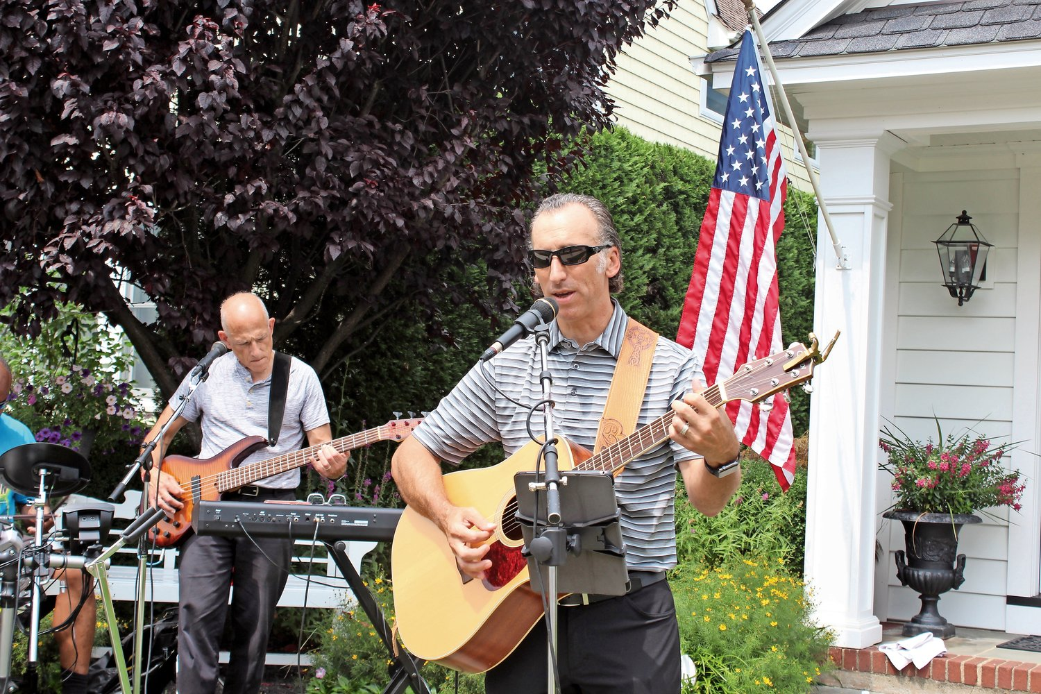 Brett Crompton, senior pastor at Church of the Intercessor, right, rehearsed with Joe Ciccarello, the Malverne church's music director in front of Bill and Lisa Wahlig's home on Wallace Street in the village.