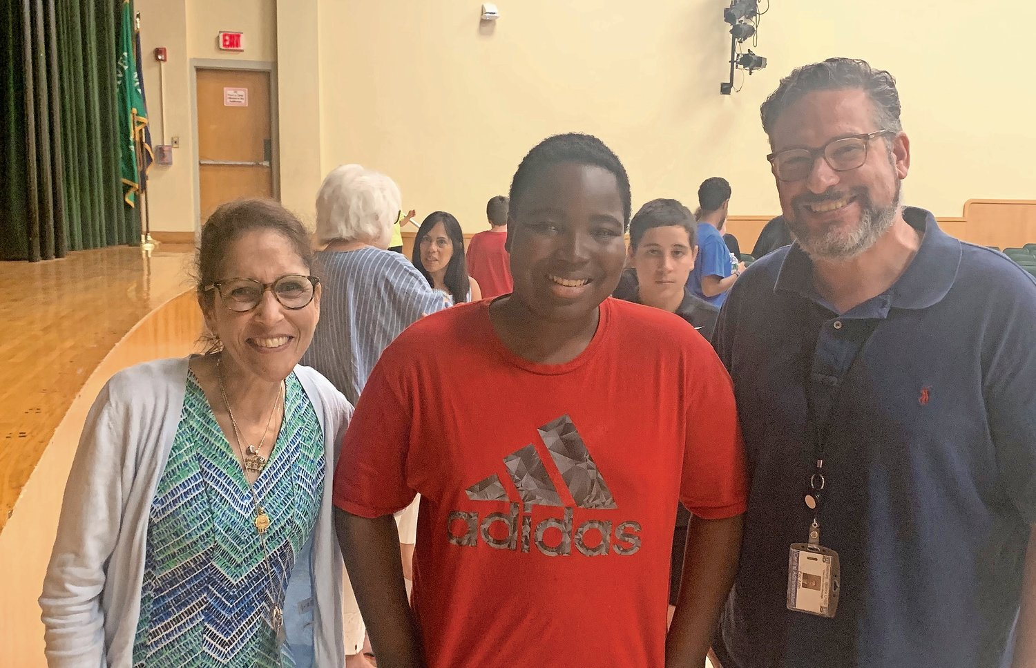 Several district officials celebrated the film's premiere, including Deputy Superintendent Mara Bollettieri, left, who congratulated Jovan O'Neal (the Mad Hatter) and Special Education Director Eric Arlin (the Red Queen's assistant).