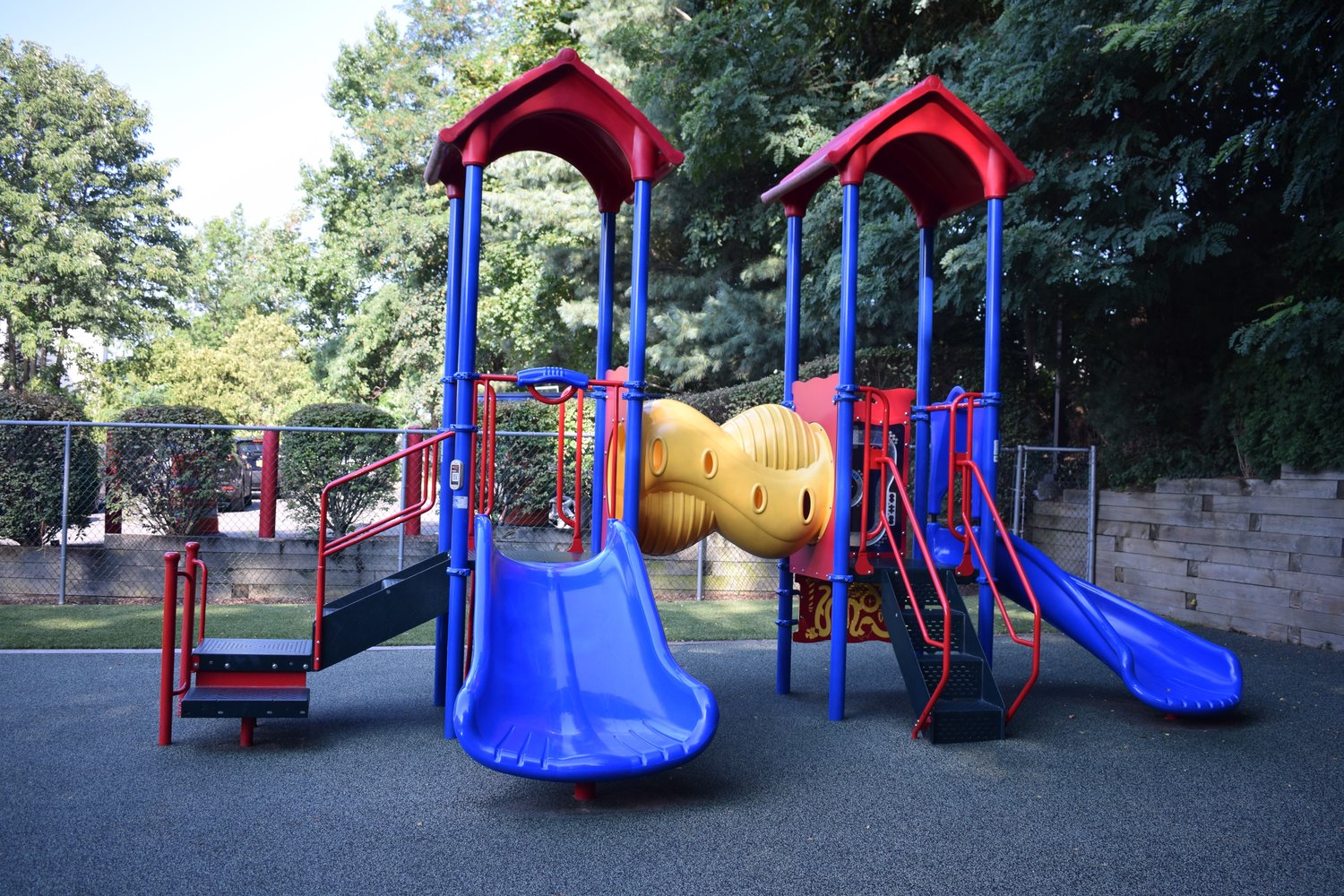The playground includes a jungle gym near the back corner of the play area.
