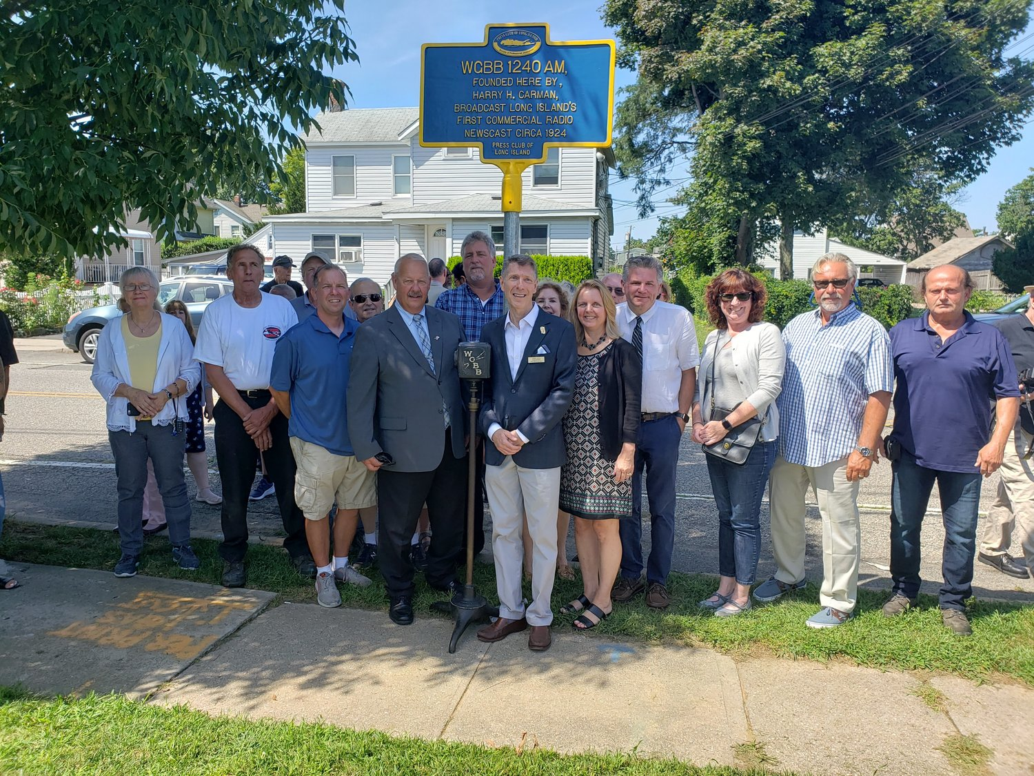 Members of the Press Club of Long Island, along with former journalists, local elected officials and members of the village's Historical Society and Landmarks Commission, gathered beneath the new WGBB historical marker.