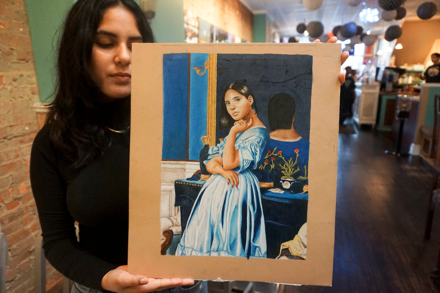 Recent Central graduate Paula Guevara with her favorite self-portrait, which she worked on for five months.