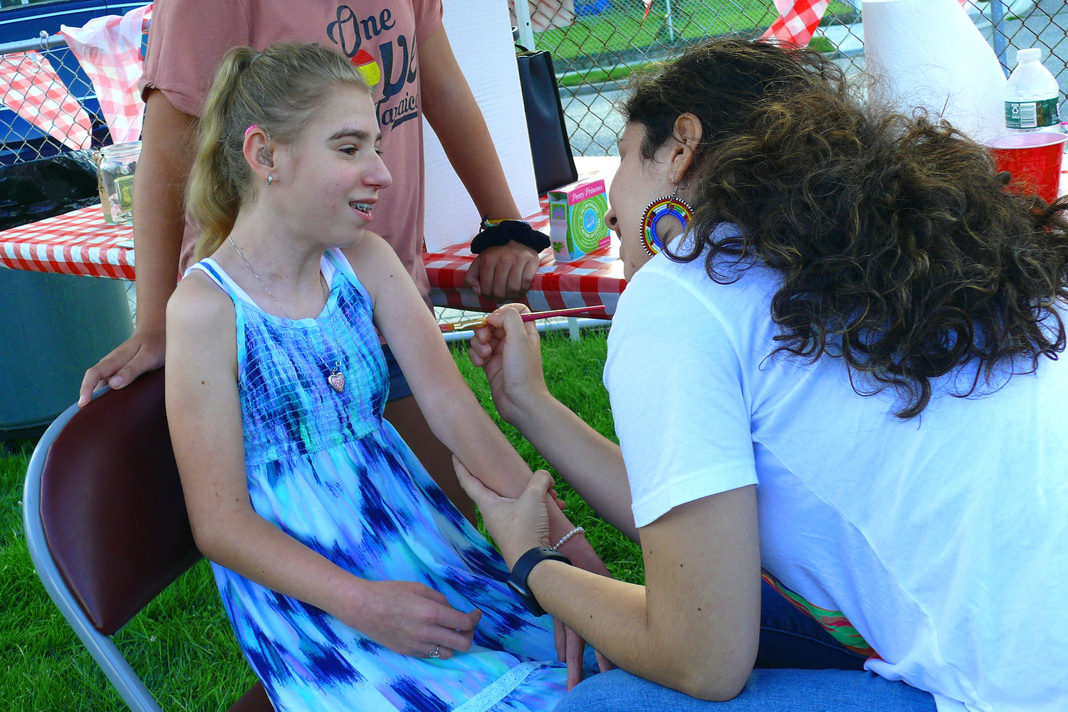 Olivia Mauro, daughter of last year's renovation recipient Keith Mauro, had her arm painted by artist Camila Merchan.
