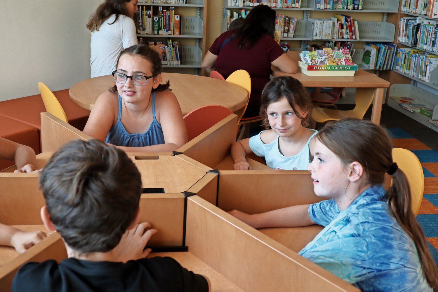 Brigid, Erin and Colleen Flanagan, left to right, rushed to the revamped kids' corner in the newly constructed North Bellmore Library.