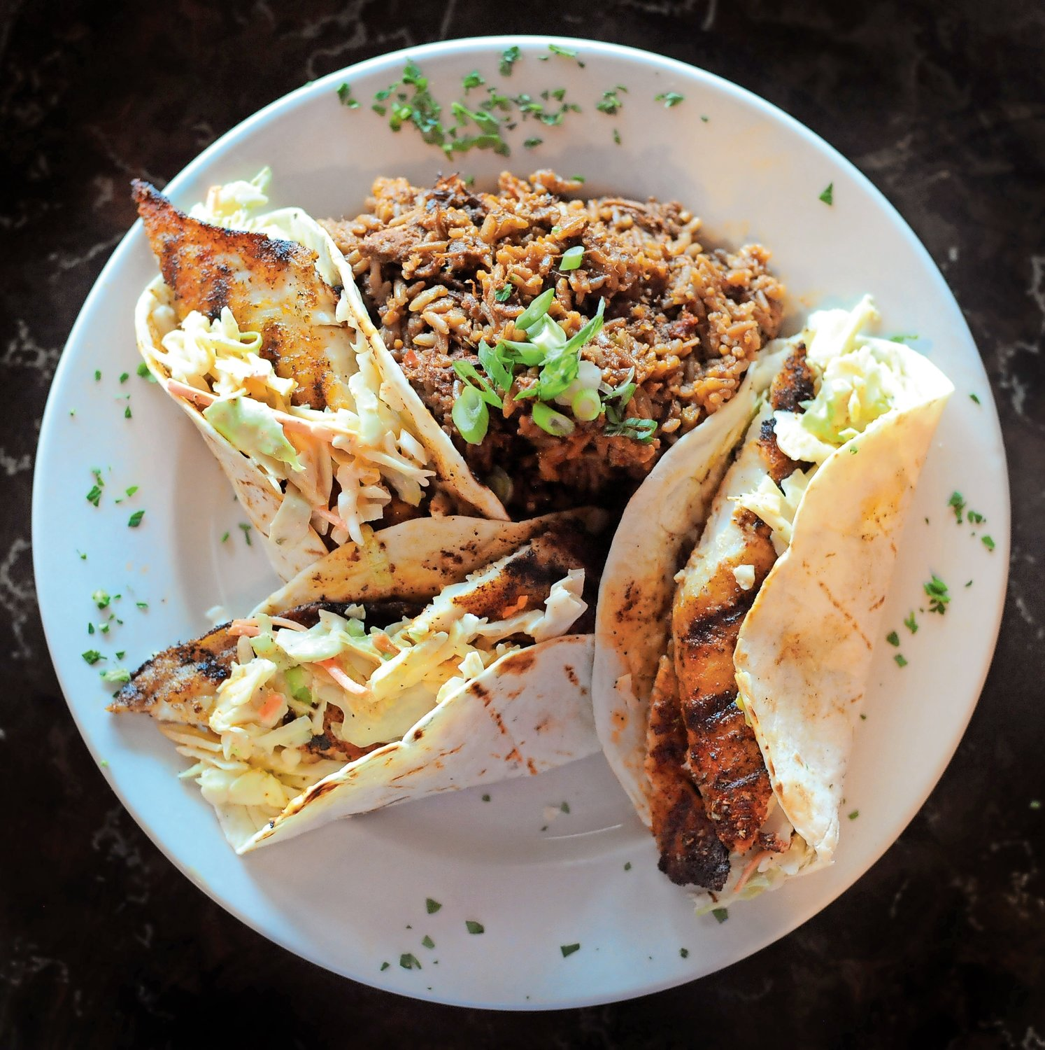 Blackened catfish tacos, served with a side of jambalaya, are a modern twist on a cuisine favorite.