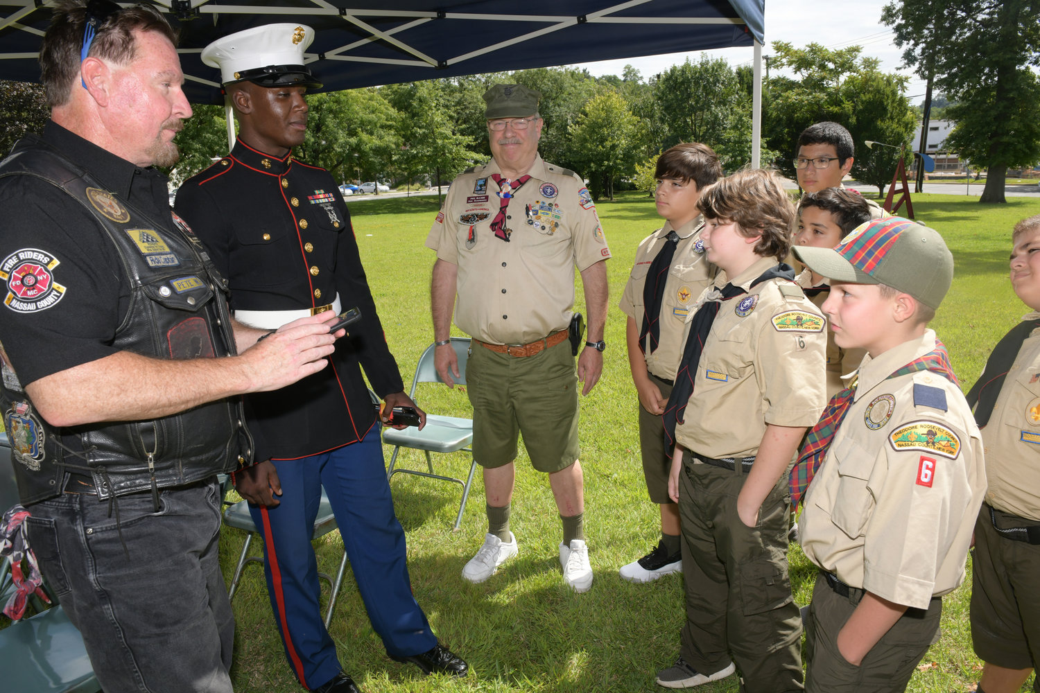 Nassau County Fire Riders Captain Pete Wenninger, left, and Sgt. Philip Smile spoke with Phillip McCabe's Boy Scout troop about the importance of the memorial.