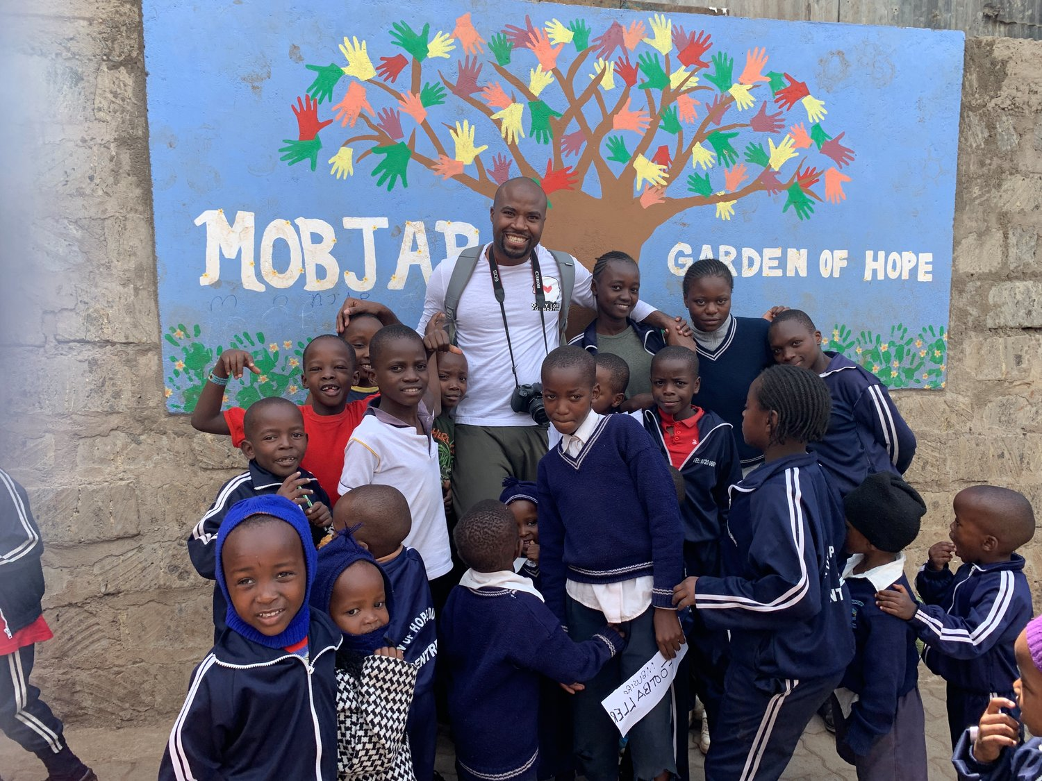 "Valley Streamer Craig Taylor with children from Kibera, Kenya, in front of a poster entitled, ""Garden of Hope."" His charity seeks to improve communities around the world, focusing chiefly on children."