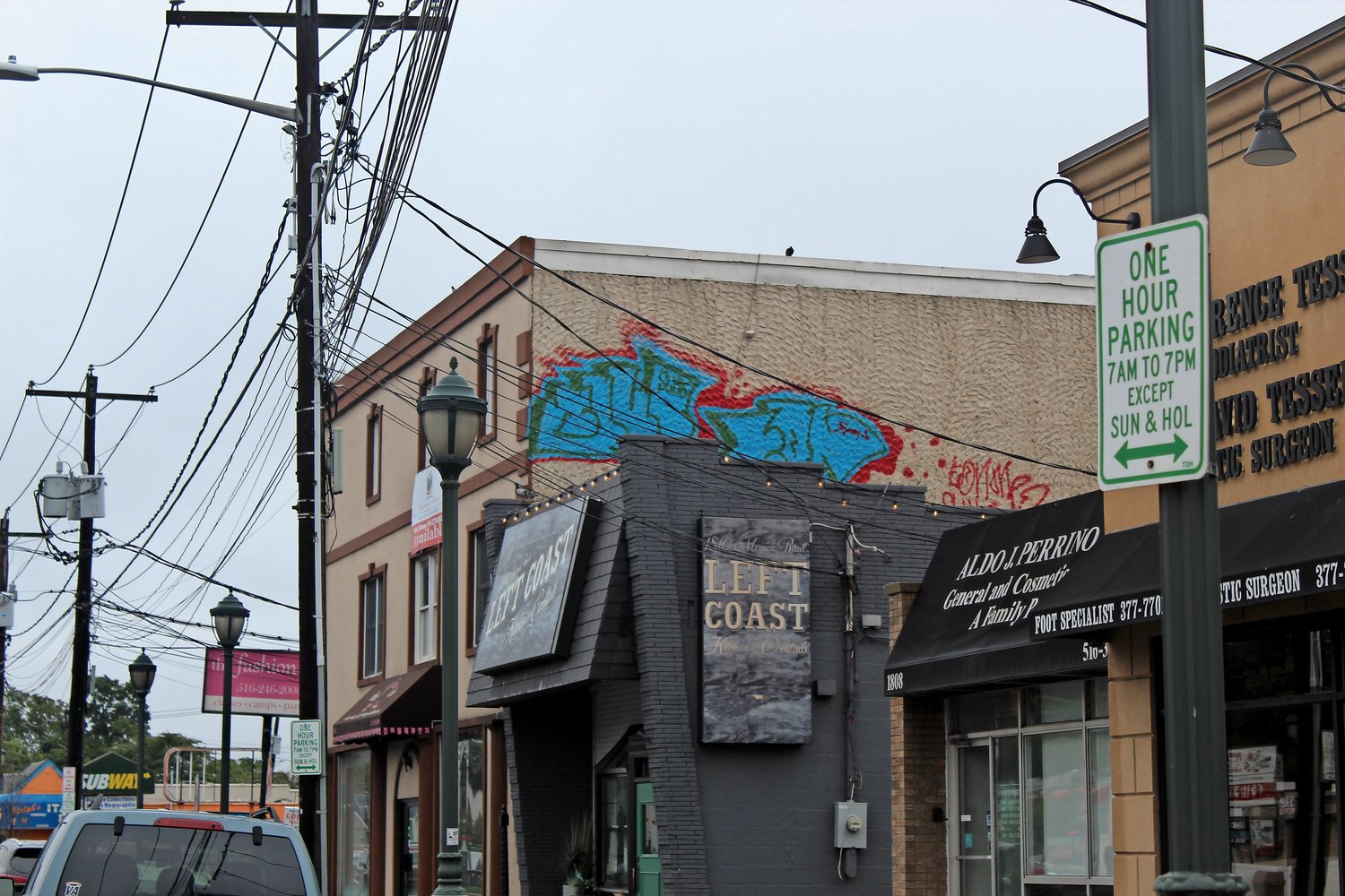 A sidewalk view of the graffiti, which is located on a wall above Left Coast Kitchen & Cocktails.