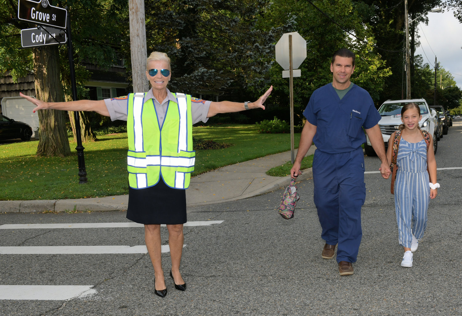 Crossing guard Mili Zilinski, helped Boz and Noreen Alissa cross the street on the way to school.