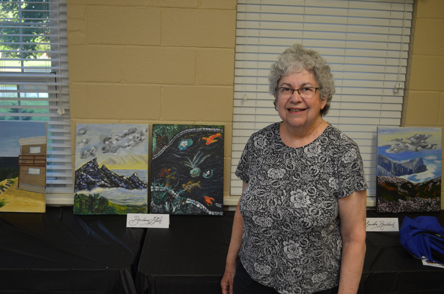 Artist Barbara Stein with her paintings. Each student spent five-weeks per work.