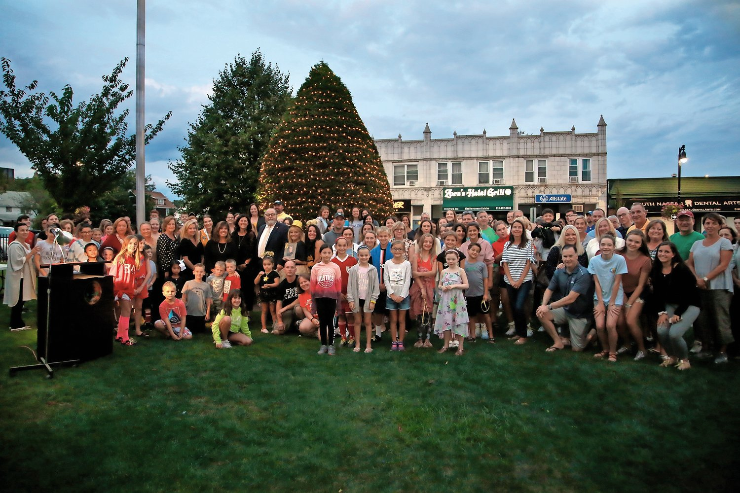 Family members and supportors of children lost to pediatric cancer, along with Mayor Fran Murray and Village and elected officials, lit the Village tree in gold.