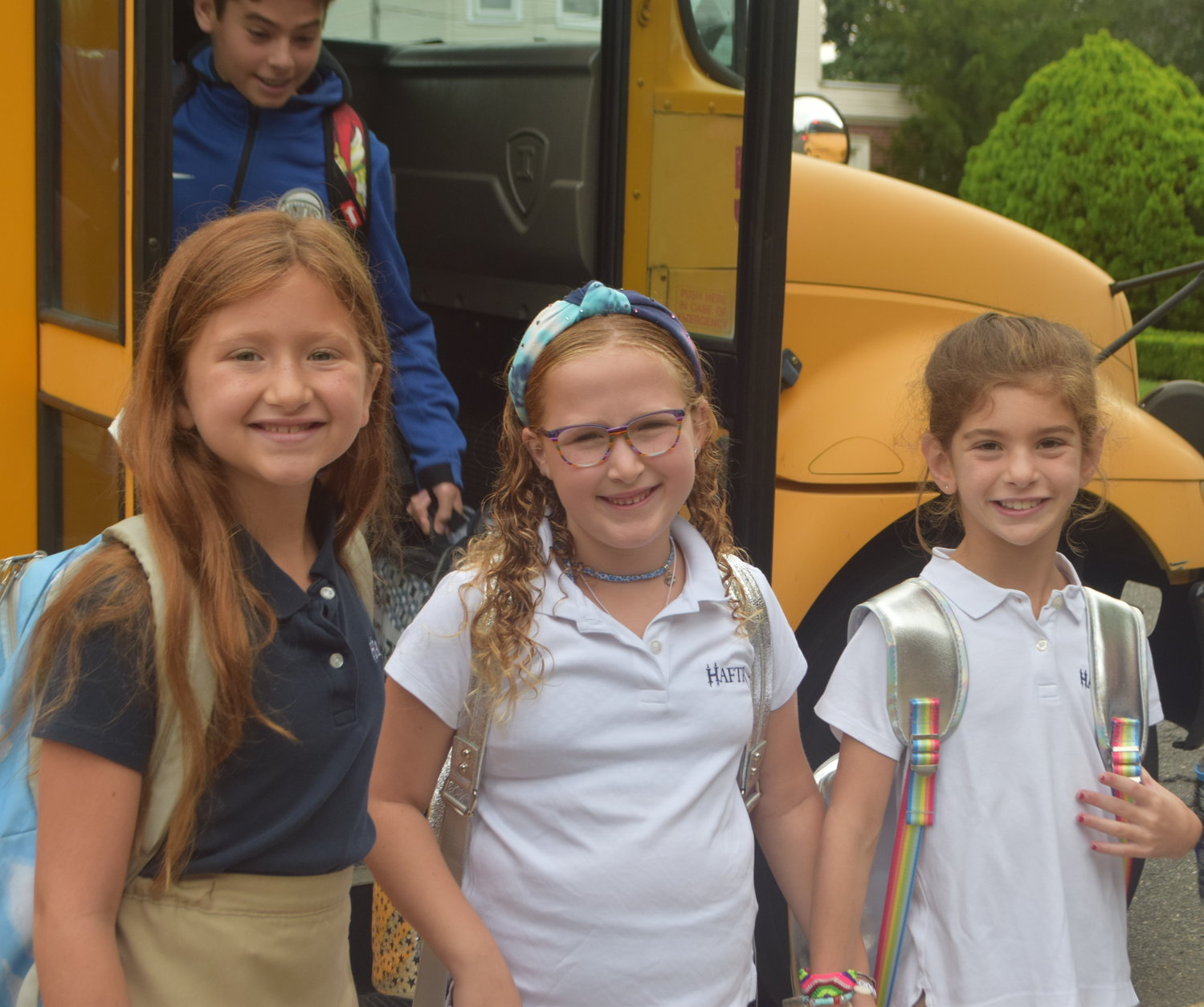 HAFTR third-graders Michelle Hersh, 8, Juliet Weinrib, 7 and Grace Rosenberg, 8, just off the bus on the first day of school, Sept. 4.