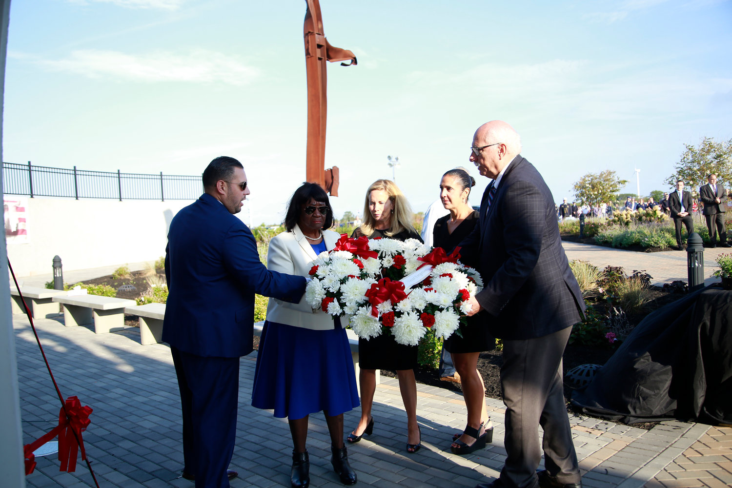 Town Council members Anthony D'Esposito, far left, Dorothy  Goosby, second from left, and Dennis Dunne, far right, joined Town Supervisor Laura Gillen, center, and Town Clerk Sylvia Cabana, second from right, to place a special wreath next to the Memorial Wall at Point Lookout Town Park.