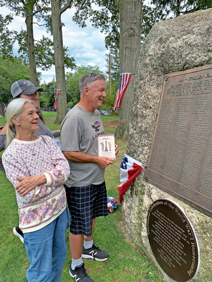 Lia Buffa, left, Joni Sturge and Mike Cain discussed the stories of the 177 soldiers on the memorial rock's plaque.