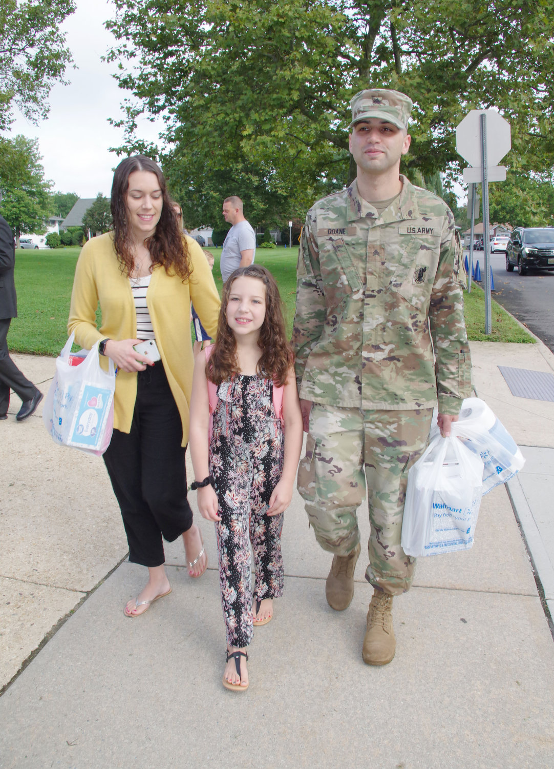 Delaney Doane, a second-grade student at Barnum Woods Elementary School, center, was with her parents Lyndsay, left and Michael on her first day of classes on Sept. 4.