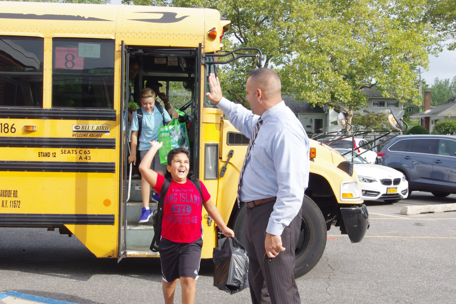 Adam Menwer, a fifth-grade student, gave a high-five to Principal Gregory Bottari after getting off the bus.
