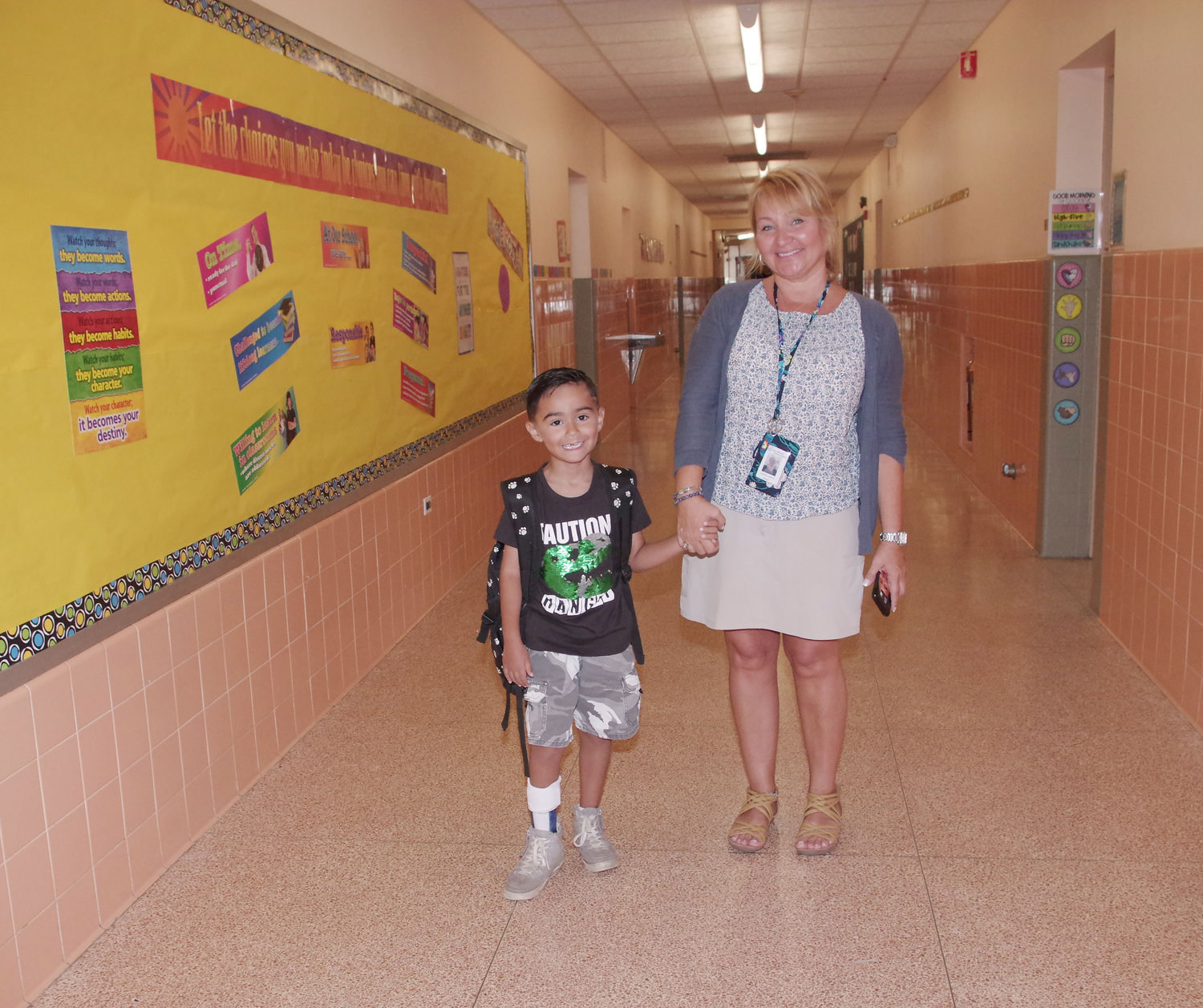 Connor Koshy, 6, was walked to class on his first day by Christine Larocca.