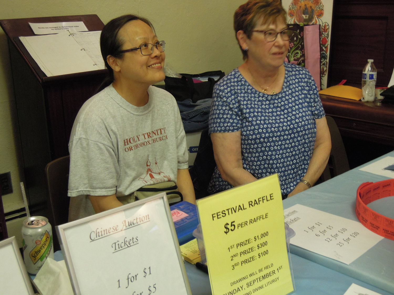 Nancy Geng Vassilakis, left, and Maryann Crowley surveyed the items for sale in  an array of items to be auctioned in various combinations.