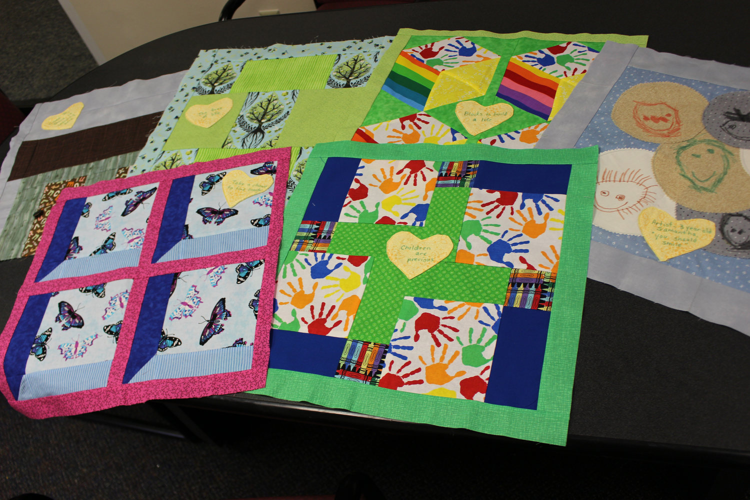 "Some of the squares from in the 1,700-piece ""wrapping quilt"" sewn to commemorate FCA's 135 years."