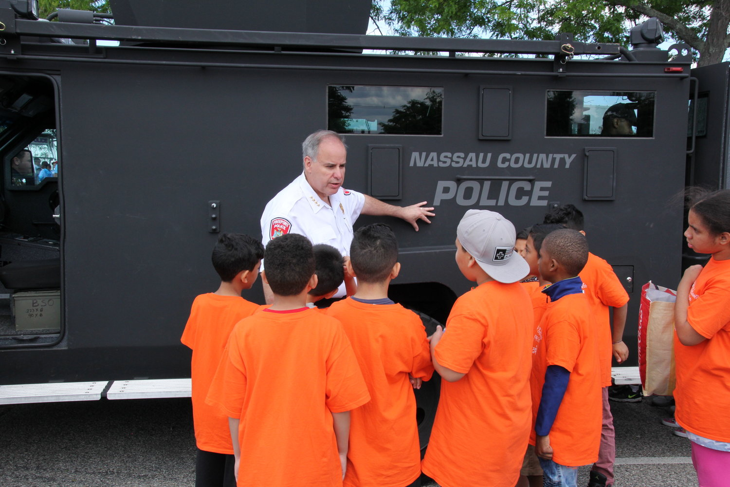 Freeport Police Chief Miguel Bermudez, shown here with students taking part in the local Adopt-A-Cop program, has announced that he is retiring from the Police Department this month.