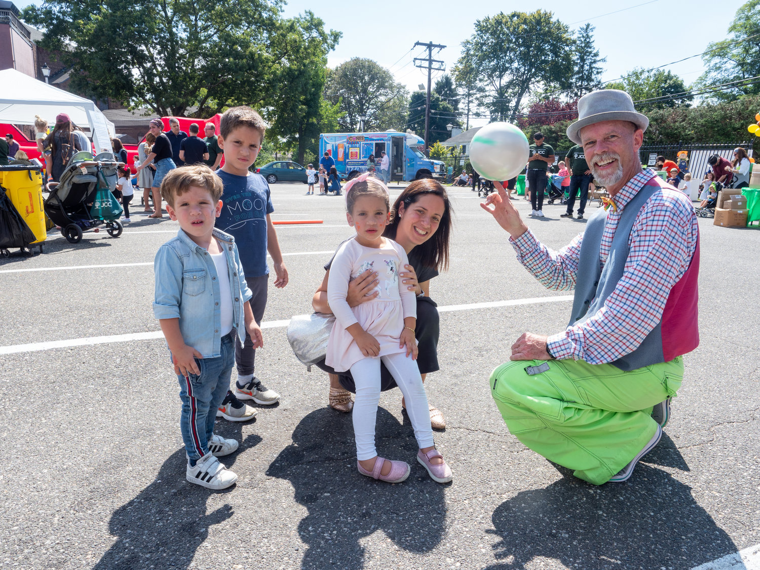 Performer Fred Collins, far right, entertained the Tawil family from left Jake, 2, Sam, 5, Linda, 4, and mother Karen at the JCC's inaugural fall festival on Sept. 15.