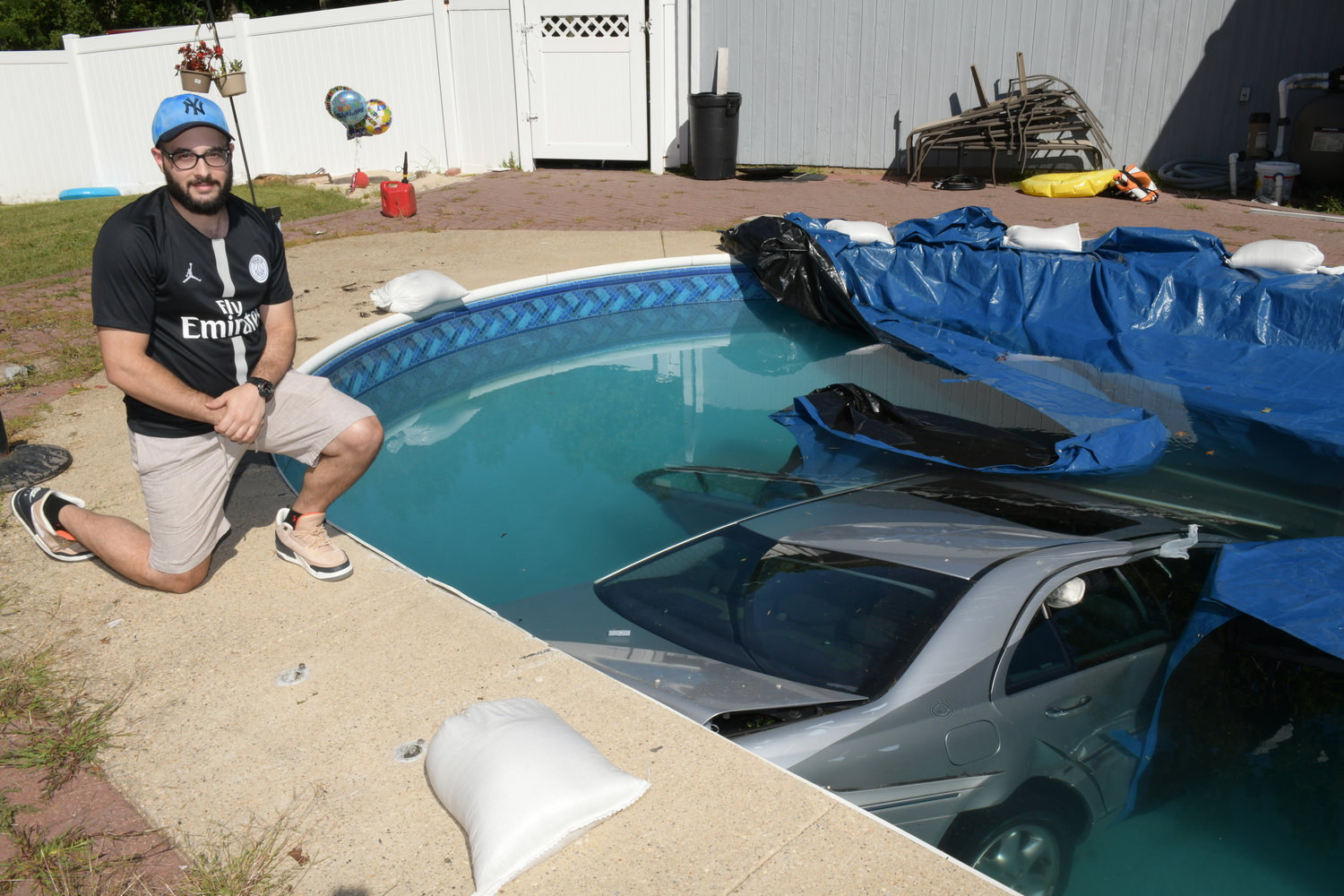 Christian Floro dove into the pool to rescue a 73-year-old woman trapped inside her car.