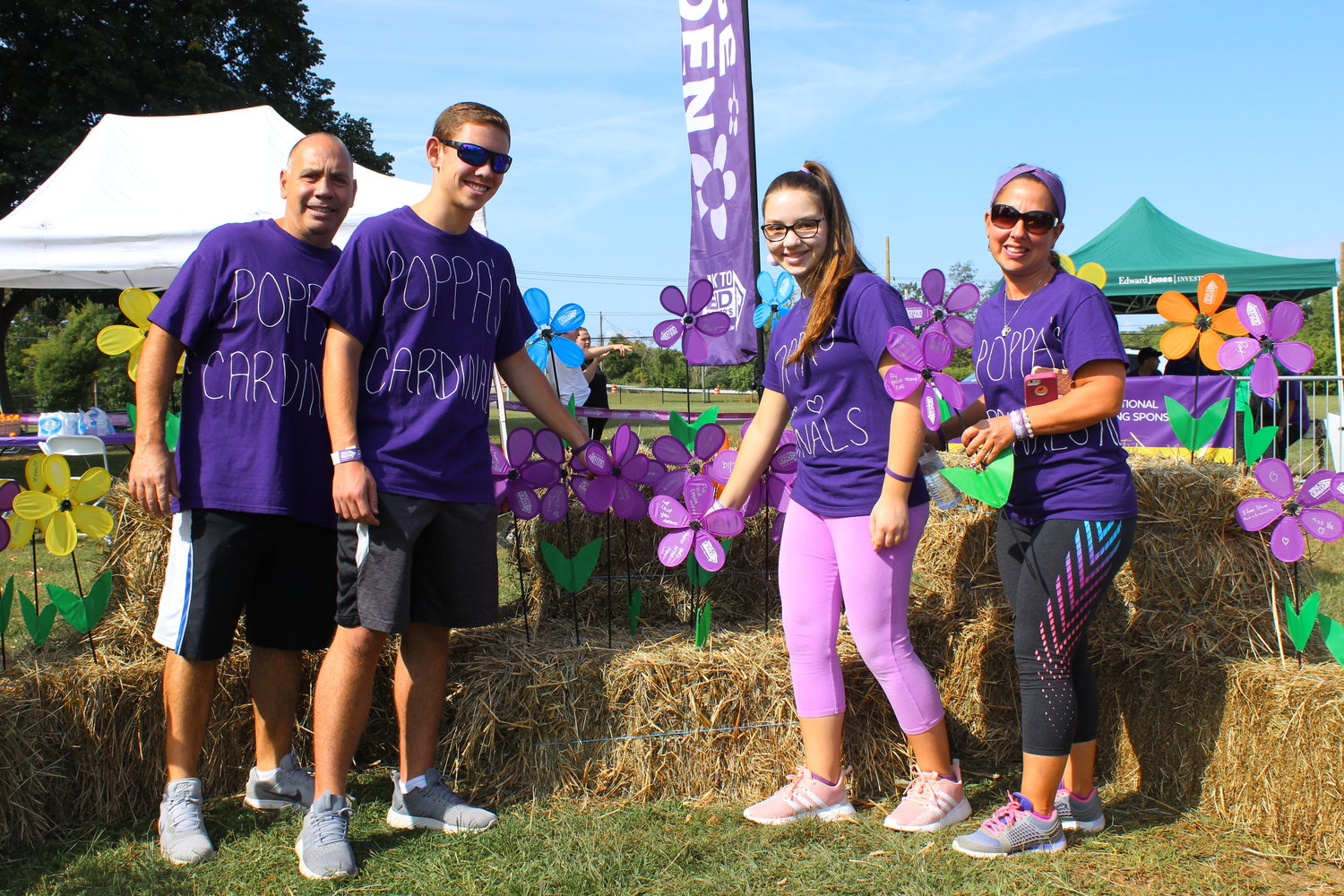 "Tommy Alcamo, his children CJ and Nicoletta and his wife Christa placed purple flowers in the ""flower garden"" at the Alzheimer's Association's 2019 Eisenhower Park walk on Sept. 15. They walked with the team ""Papa's Cardinals"" to commemorate Christa's father Eugene Negri, who died three years ago after a long battle with Alzheimer's disease. He was 77."