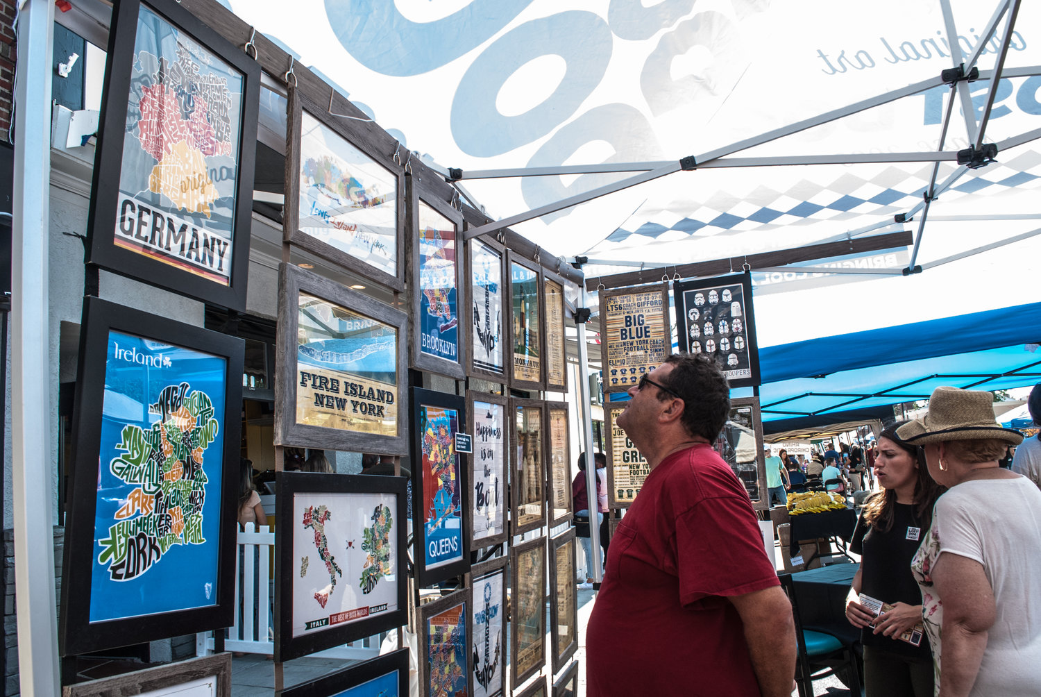 Steve Cosares takes an interest in the graphic designs of many LI towns at the tent of The Lost Dog Art & Frame Co.