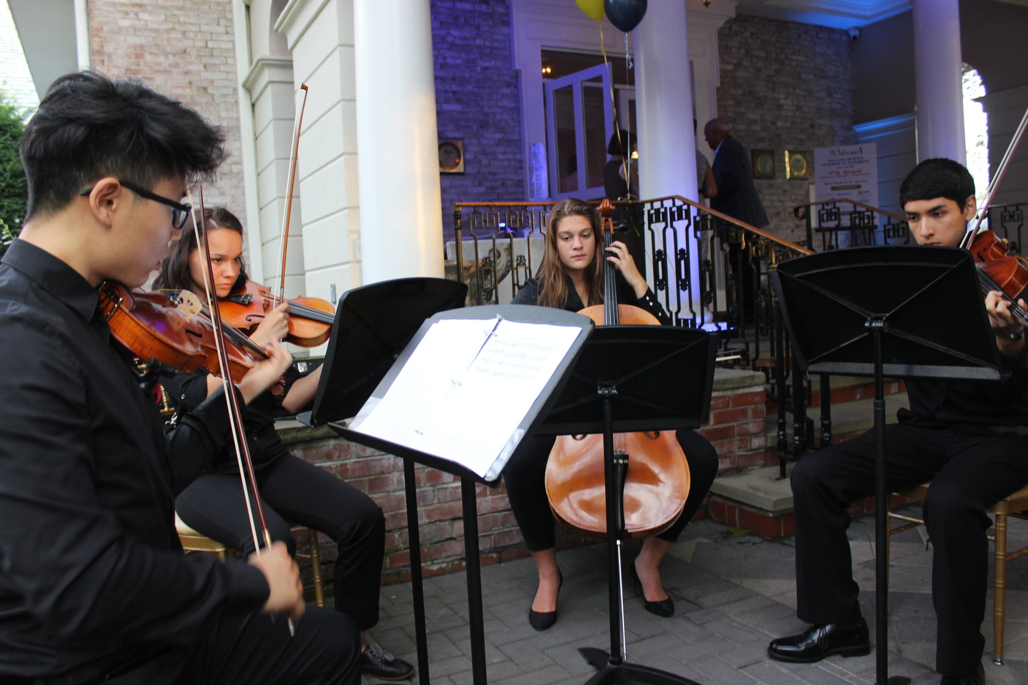 Outside the Carltun, guests were serenaded by a string quartet comprising, from left, Lucas Mun, Yana Vilchynskaya, Vanessa Froehlich and Joaquin Caceres, all members of the East Meadow High School Chamber Orchestra.