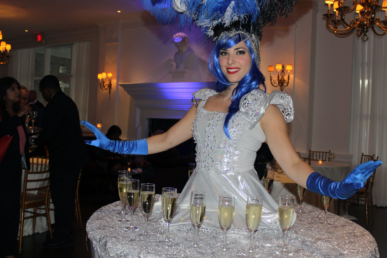 "A performer wore a shimmering ""champagne dress"" that was fastened to a table and lined with glasses of champagne that she served to guests."