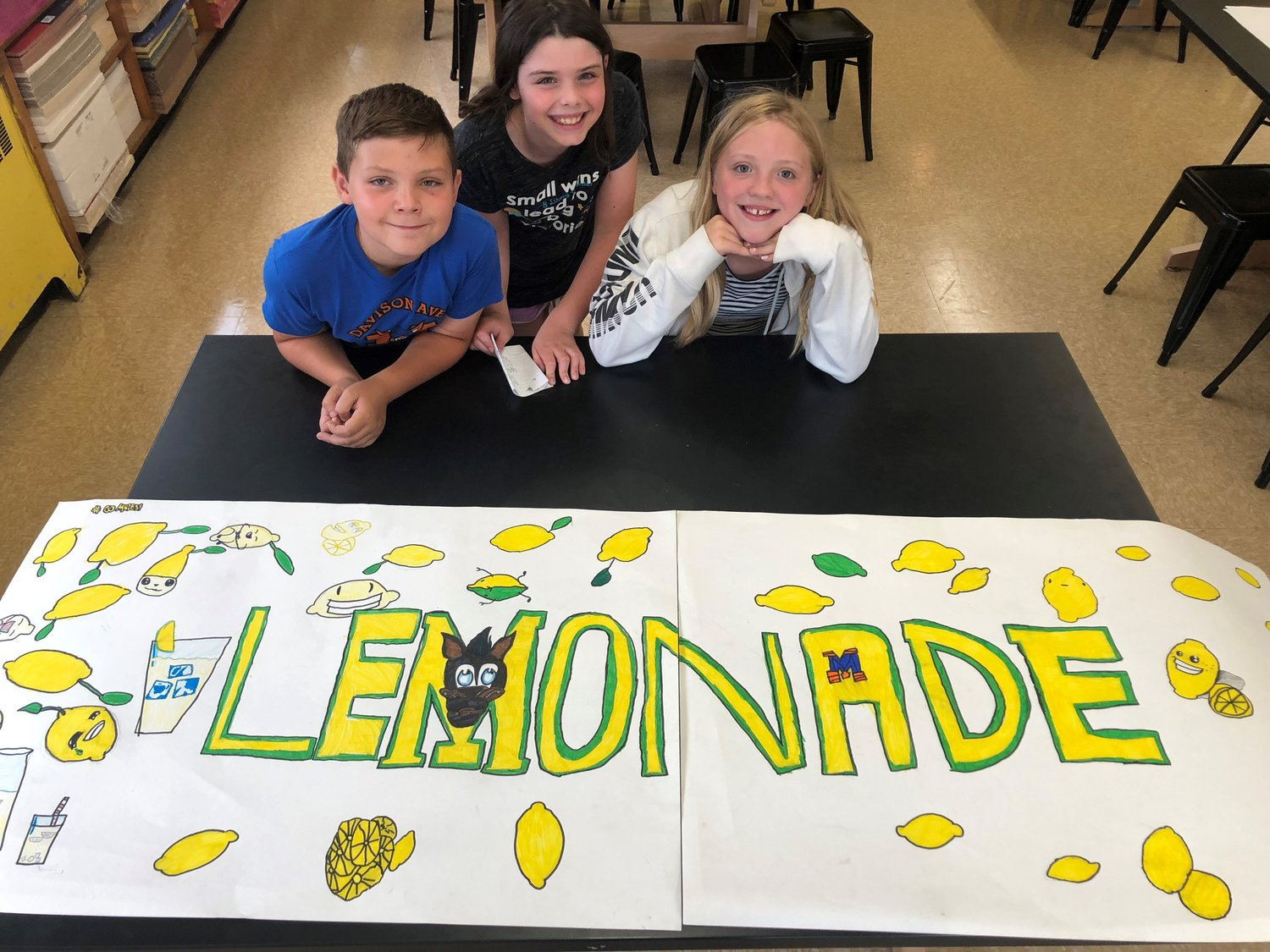 Davison Avenue School students Luke Major, left, Maeve Schumacher and Kate Wolff helped to set up a lemonade stand to raise funds for the Alex's Lemonade Stand Foundation last month.