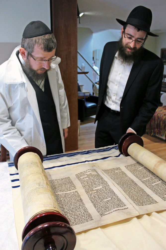 Rabbi Shimon Kramer and Cantor Nissen Pewzner admired the Kristallnacht Torah.
