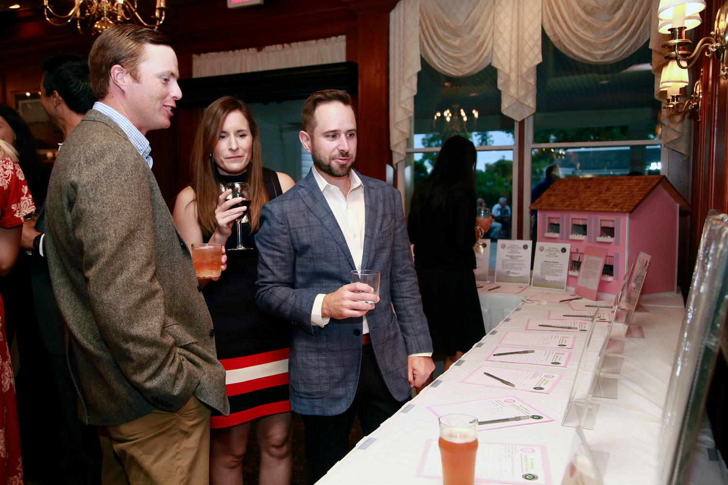 Benjamin Pellicani and Crissy and Anthony Boyer look over the silent auction items.