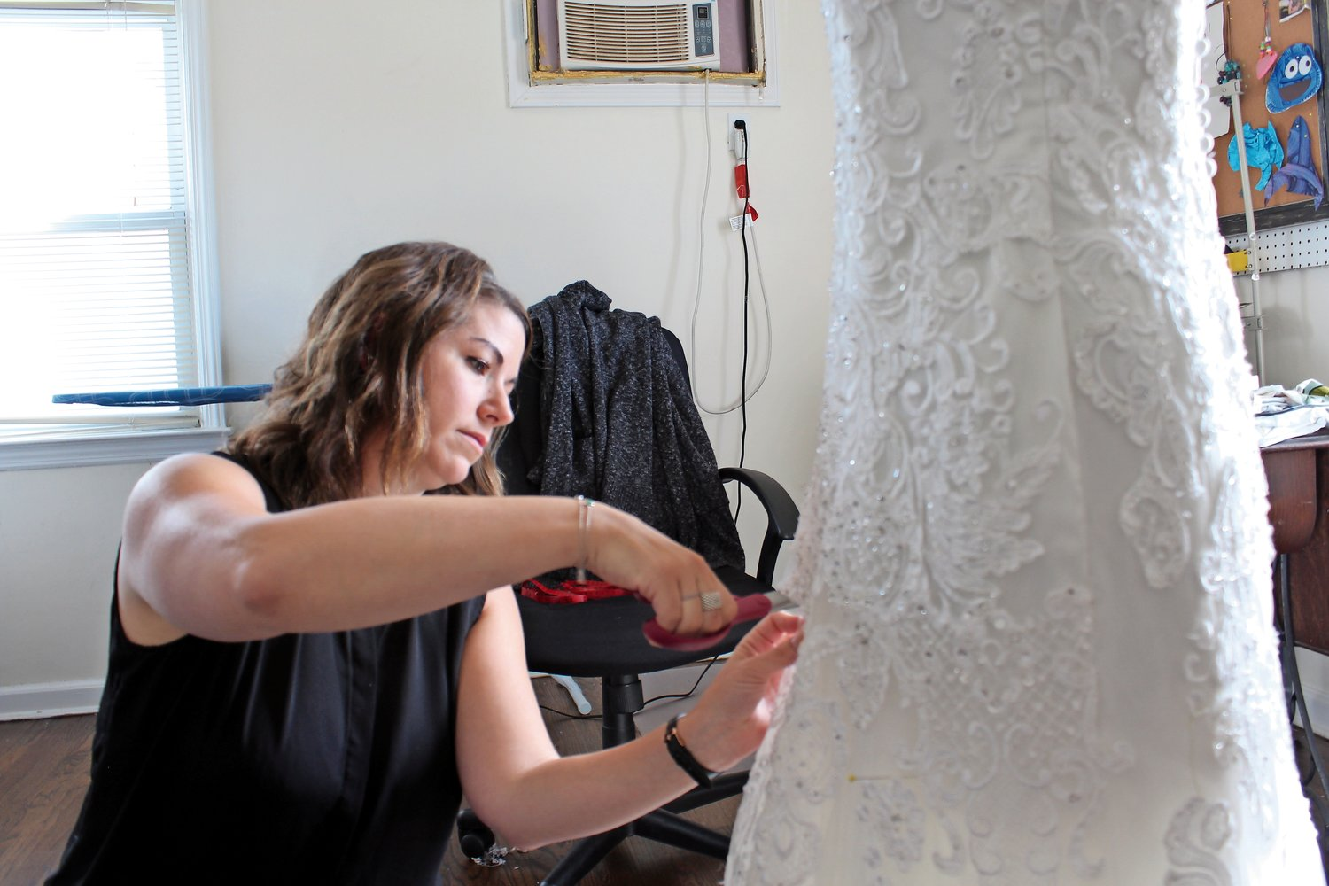 Cat Munzing cut a client's dress, the first step in repurposing it to create a christening gown for the woman's daughter.