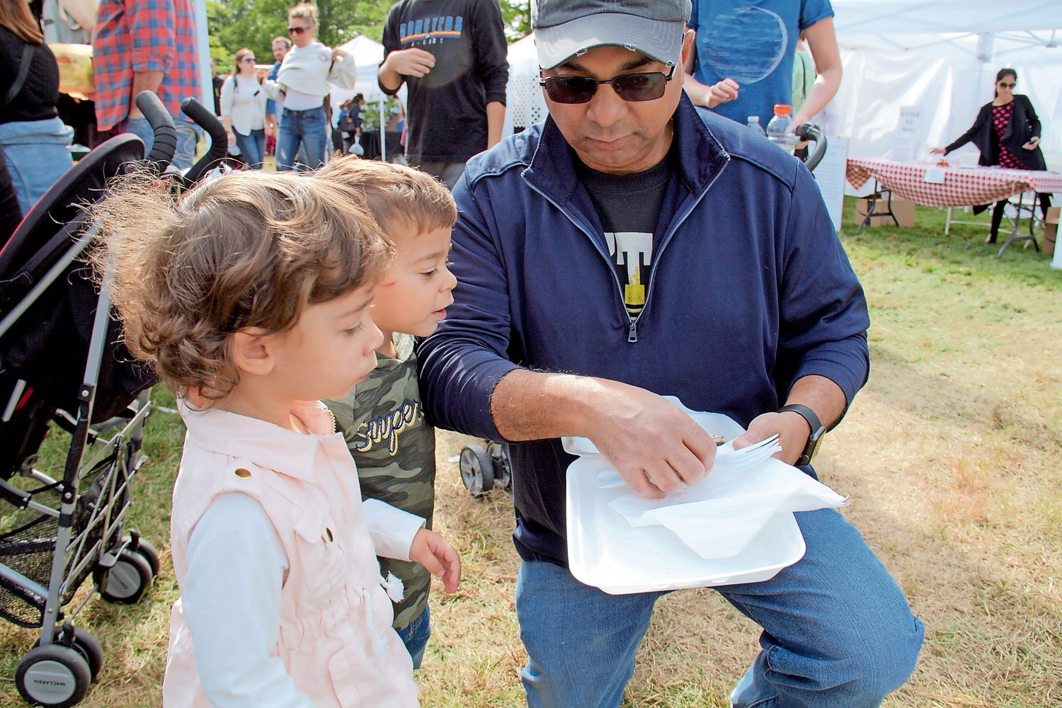 Two-year-old twins Emma and Jake DiFiglia tasted a blueberry crepe for the first time that their father Sam bought at the festival.