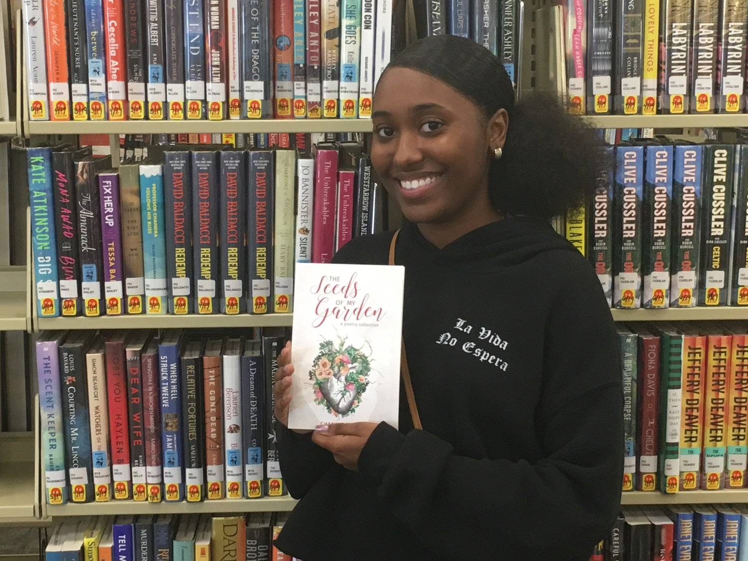 "Freeporter Channie Maria, 27, donated an autographed copy of her collection of poems, ""The Seeds of My Garden: A Poetry Collection."""