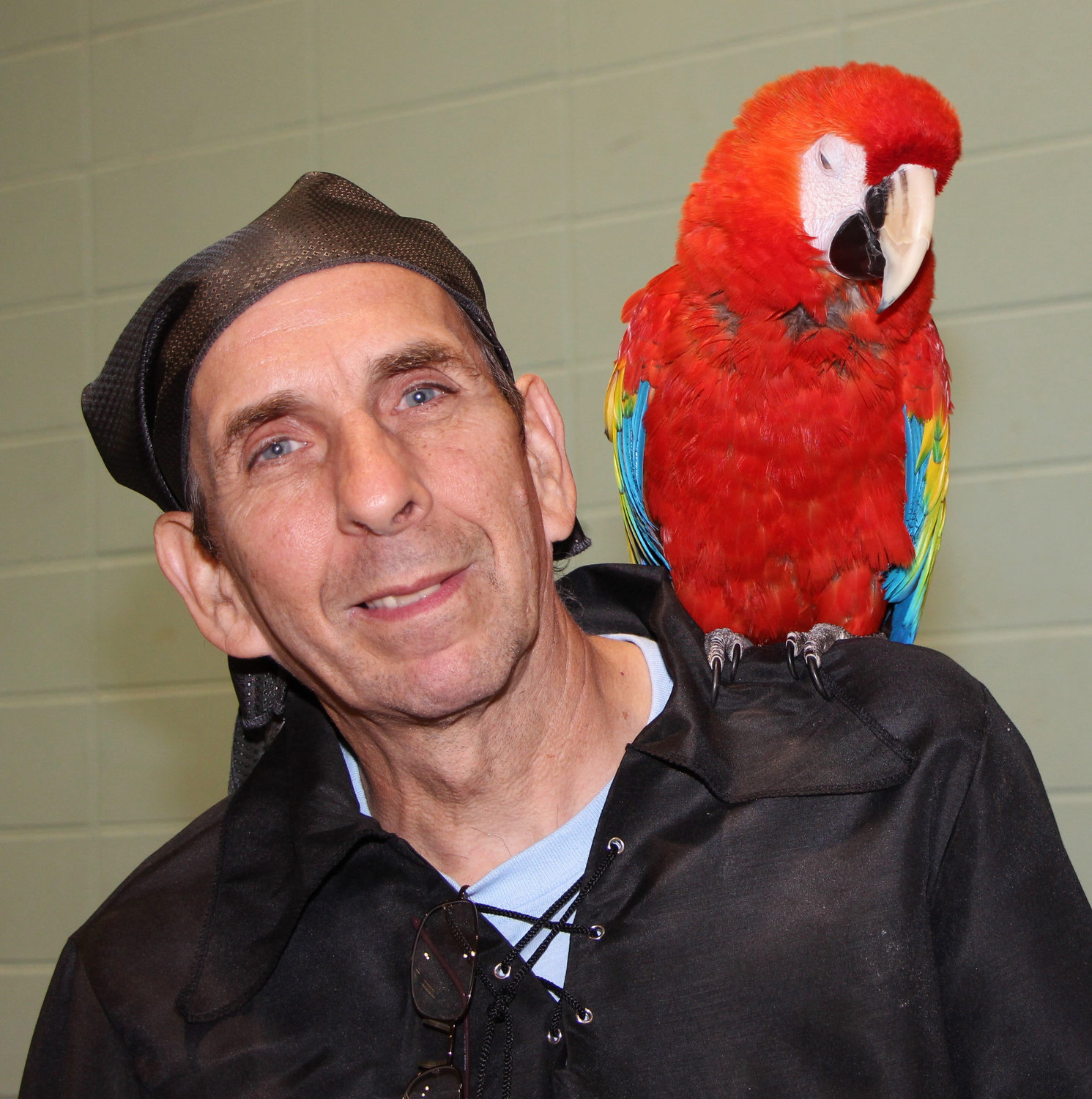Frank Huwer with one of his many birds, Aries, a scarlet macaw.