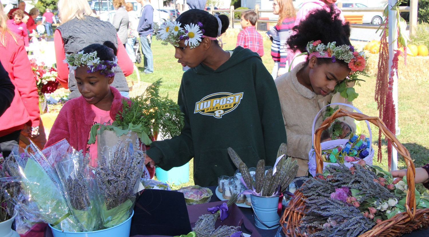 Delila Stevens, 8, left, and her sisters Desarae, 10, and Gabriella, 9, wore floral crowns and looked through dried flowers at the East Meadow Farm's annual Family Fun Day.