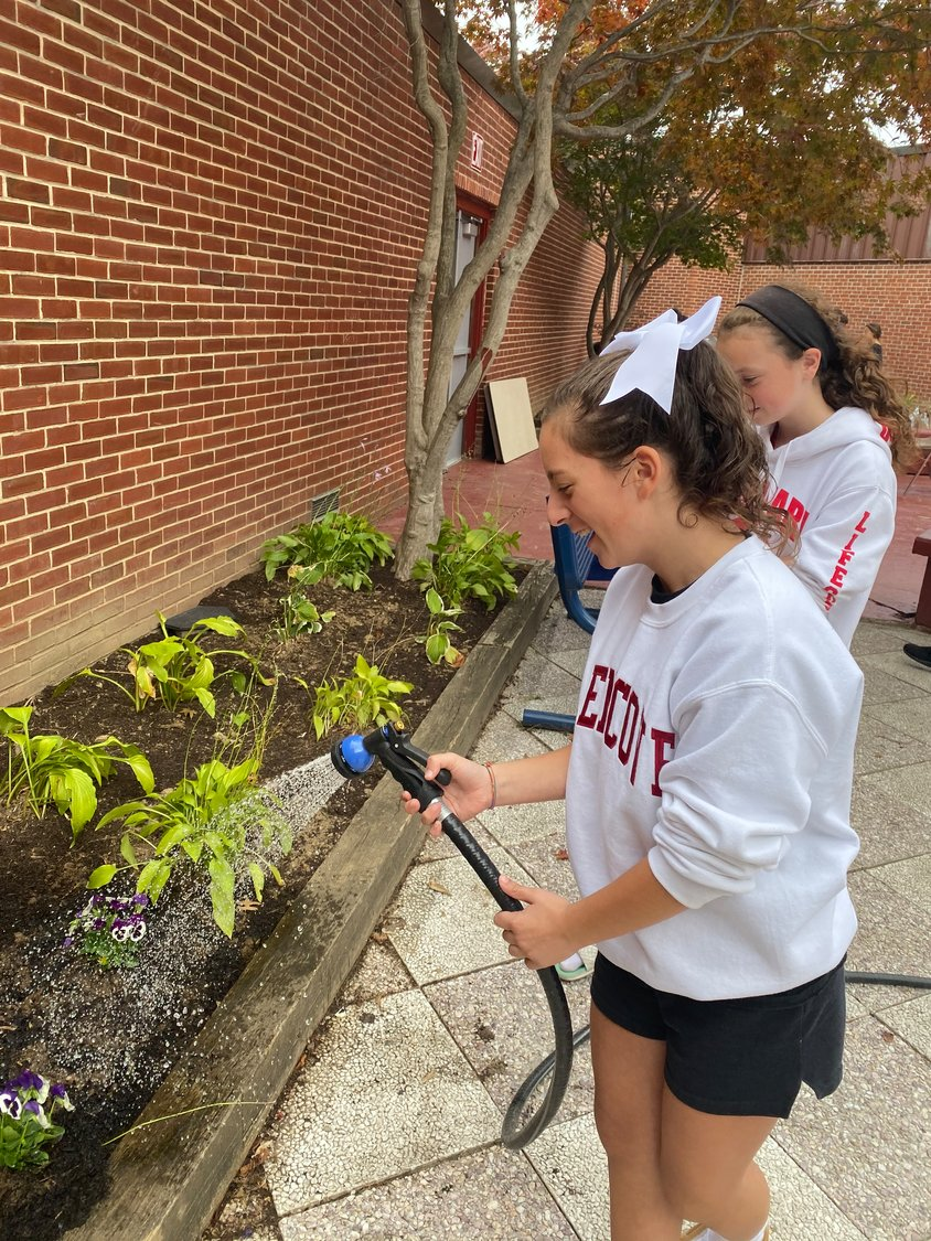 Sofia Greco, left, and Ava DeLuca helped water the garden at the new student lounge at the Robert M. Finley Middle School.