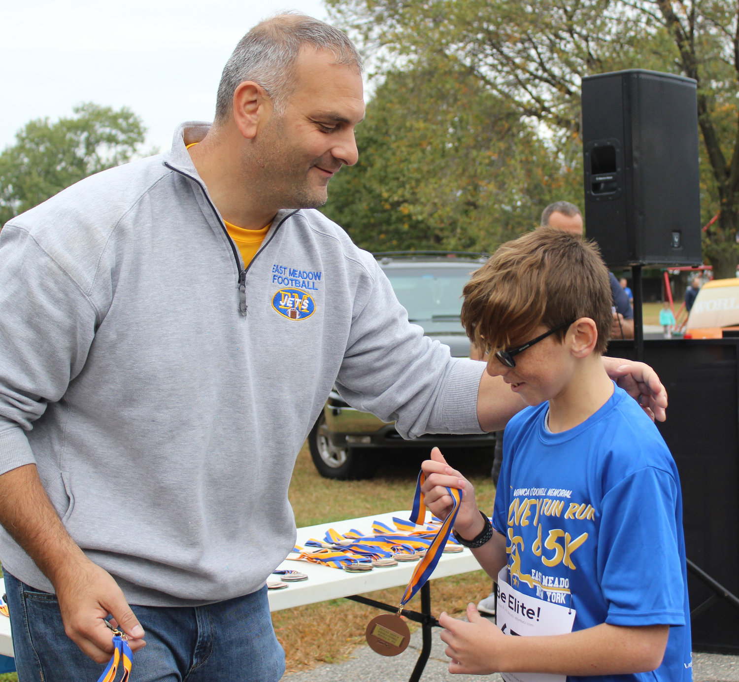 Race organizer Michael Simone, left, congratulated Quinn Giblin, 14, who finished third among boys 14 and under.