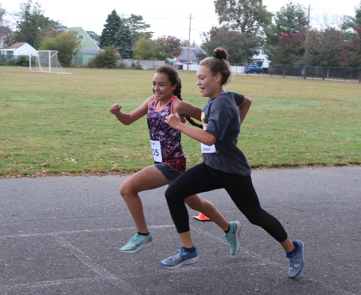 Ella Foster and Leslie Villafuerte, both 15, neared the finish line, above. Both runners are on the East Meadow High School cross-country team, and entered the race for some friendly competition.