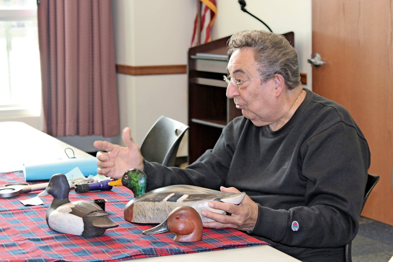 Eddie Costello Sr. appraised wooden ducks at the Elmont Memorial Library on Oct. 26.